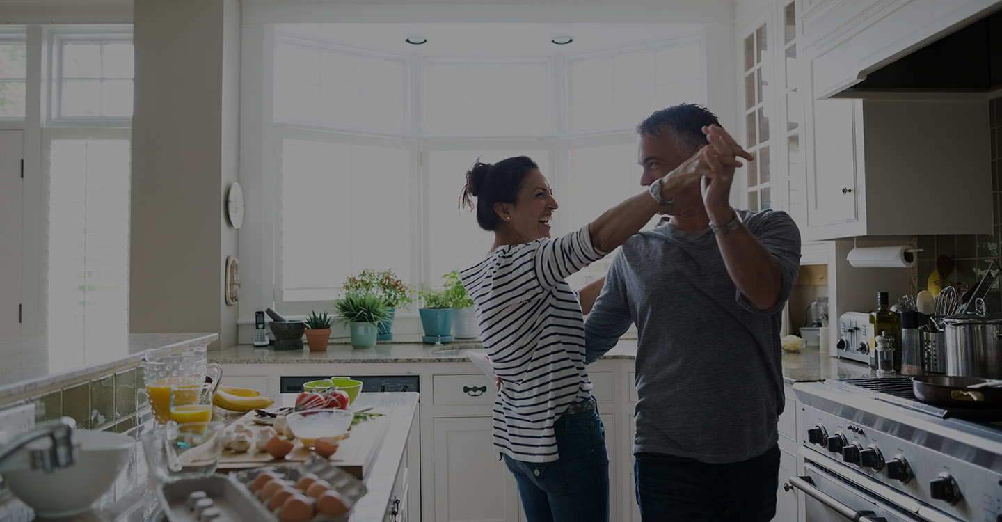 Couple dancing in kitchen for spine health